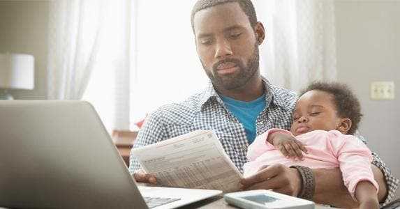 Dad reading bill while holding baby   KidStock/Getty Images
