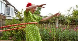 Senior woman in polka dot dress hula-hooping | David Woolley/Getty Images