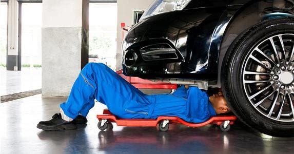 Auto mechanic working on car in shop | Twinsterphoto/Shutterstock.com