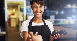Woman holding chip card reader © Uber Images/Shutterstock.com
