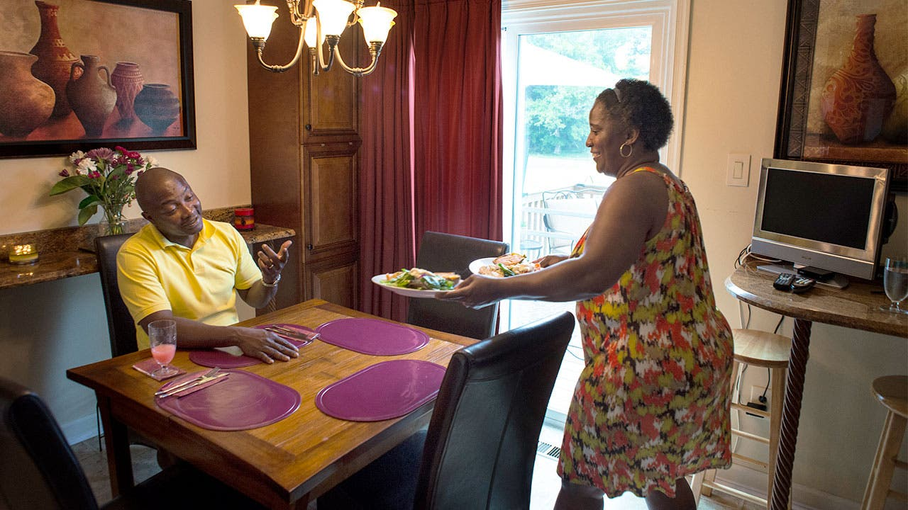 Woman putting meal on kitchen table where man is sitting