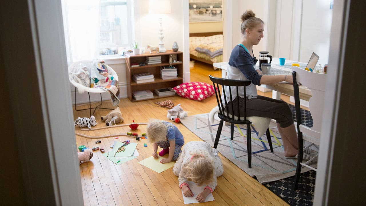 Mother at her home computer with toddlers behind her | Hero Images/Getty Images