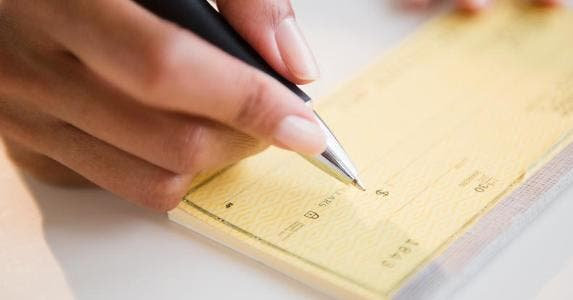 Woman writing amount on check | JGI/Jamie Grill/Blend Images/Getty Images