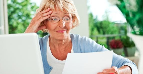 Woman looking unhappily at her bill © iStock