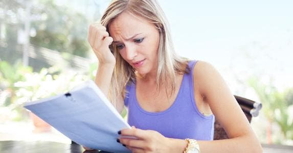 Worried woman looking at letter or statement © iStock
