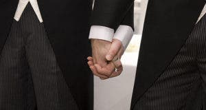 Two men wearing suits holding hands © govicinity/Shutterstock.com