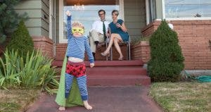 Little kid in superhero costume with parents in front porch | FogStock/Vico Images/Aisha Harley/Getty Images