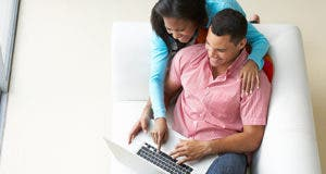Couple sitting on couch with laptop © Monkey Business Images/Shutterstock.com