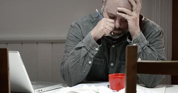 Stressed man in dining room overwhelmed with debt | iStock.com/Fertnig