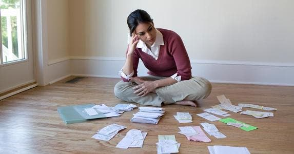 Young woman sitting on floor staring at bills | iStock.com/LifesizeImages