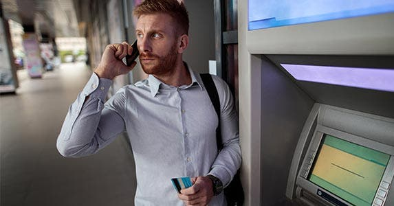 Man on phone at ATM with credit card in hand