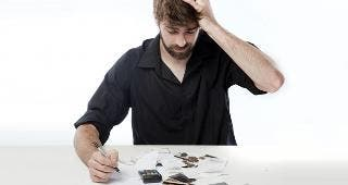Man with debt, paperwork © Danie Nel/Shutterstock.com
