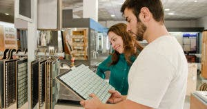 Young couple choosing tiles in home improvement store © iStock