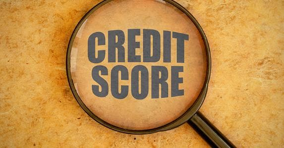 Magnifying glass on credit score, brown paper © iStock