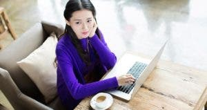 Young woman in purple sweater using laptop computer | iStock.com/visionchina