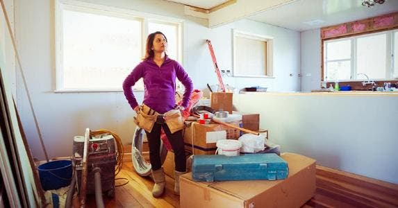 Woman standing in the middle of a room under renovation | Donald Iain Smith/Blend Images/Getty Images