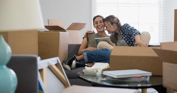 Couple laughing together while packing belongings | Hero Images/Getty Images