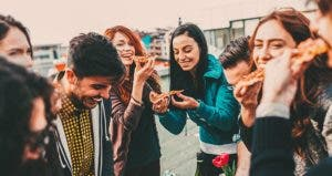 Millennials laughing and eating pizza | Todor Tsvetkov/Getty