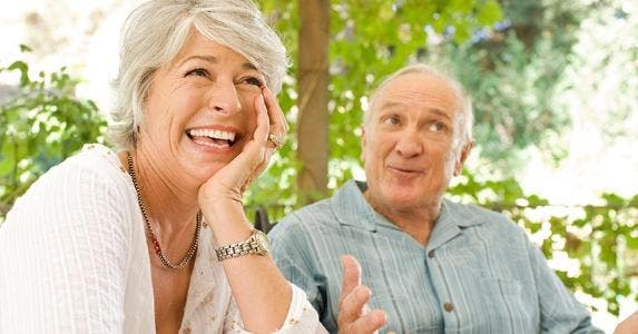 Couple sitting outside, laughing at stories | Jim Purdum/Getty Images
