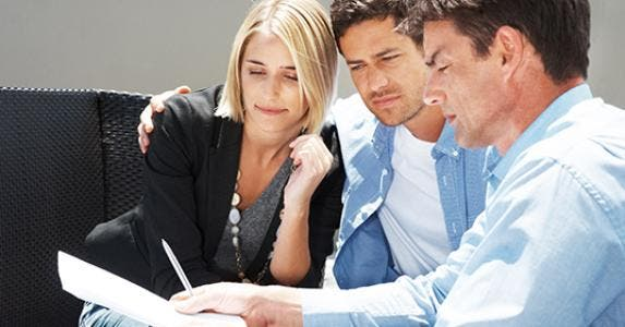 Couple reading paperwork with adviser © Fotolia.com