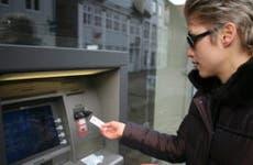 Woman taking cash from outdoor ATM © jean schweitzer/Shutterstock.com