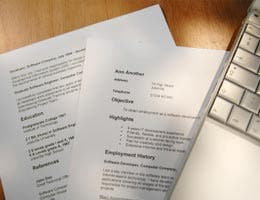 Resume with laptop on wooden table