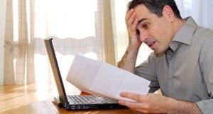 Man sitting at desk, horrified at bills © Elena Elisseeva/Shutterstock.com