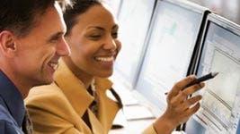 Man and woman looking at investing monitor