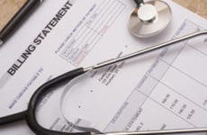 Stethoscope on medical billing statement on table © aastock/Shutterstock.com