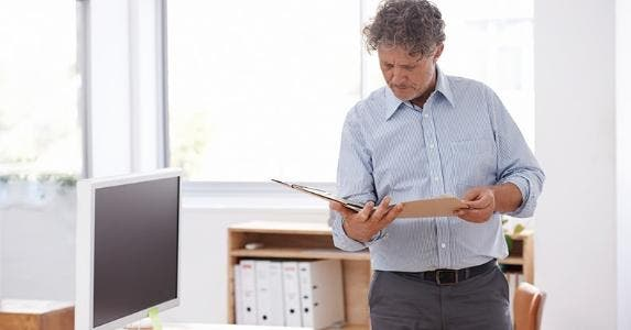 Middle aged man reading paperwork in office © iStock