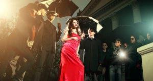 Woman in red dress posing in front of paparazzi © kuznetcov_konstantin/Shutterstock.com