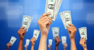 Many hands holding money in air © Silhouette Lover/Shutterstock.com