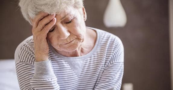 Stressed senior woman wearing striped sweater | iStock.com/gpointstudio