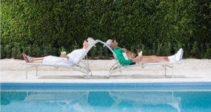 Retirees sunbathing by the pool | Image Source/Getty Images