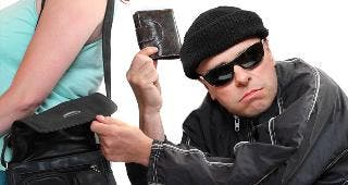 Thief stealing wallet from purse © Kletr/Shutterstock.com