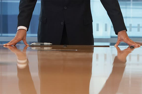 Hands on conference room table: © bikeriderlondon/Shutterstock.com; Money bag: maradonna 8888/Shutterstock.com