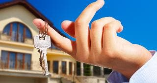 Key on finger in front of house © Gabi Moisa / Fotolia.com