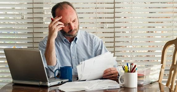 Worried mature man reading bills and papers in home office