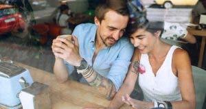 Couple seated at diner bar, laughing   popovartem.com/Shutterstock.com