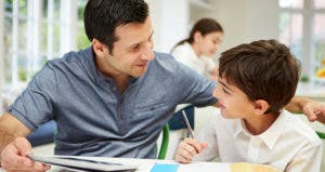 Dad helping young son with homework in kitchen table © iStock