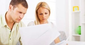 Couple seriously reading paperwork