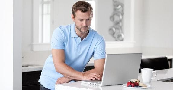 Man in blue shirt browsing computer on breakfast counter | iStock.com/BrittaKokemor