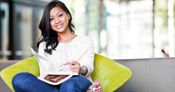 Young woman sitting on green chair, writing on notebook © arek_malang/Shutterstock.com