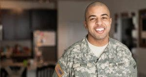 Service member smiling in his living room | Roberto Westbrook/Blend Images/Getty Images