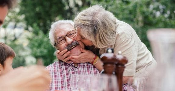 Woman kissing husband's cheek at picnic table | Sofie Delauw/Cultura/Getty Images