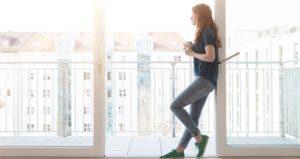 Millennial standing in frame of patio doorway | Westend61/Getty Images