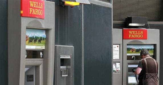 Man withdrawing from an outdoor Wells Fargo ATM | Justin Sullivan/Getty Images