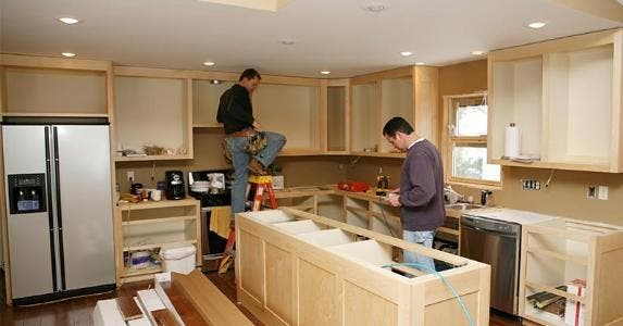Men working on cabinets for kitchen remodel | George Peters/Getty Images & How Much Does It Cost To Remodel A Kitchen?