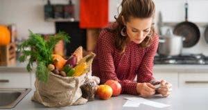 Woman reading grocery receipt in kitchen | Alliance/Shutterstock.com