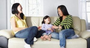 Two women laughing with little girl on couch | Camille Tokerud/Getty Images